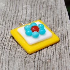 This handmade fused art glass pendant features a beautiful daisy. The pendant is fused at a lower temperature to give it a 3-dimensional look. I began by making little glass balls in the kiln. Then I tack fused the turquoise and red balls onto a white and yellow stacked base to create the daisy. The pendant is hung from a sterling silver plated bail and measures approximately 1 square.    I make all of my fused art glass using 100% compatible glass in my home studio in Jacksonville, Florida…