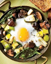 Eggs Baked Over Sautéed Mushrooms and Spinach |  1 tablespoon olive oil  1 large leek, white and light green parts only, cut into 1/2-inch pieces  1 tablespoon unsalted butter  1 pound white or cremini mushrooms, thinly sliced (about 6 cups)  1 tablespoon soy sauce  1/4 cup dry red wine  5 ounces baby spinach  Salt and freshly ground pepper  4 large eggs  4 slices of whole-grain toast