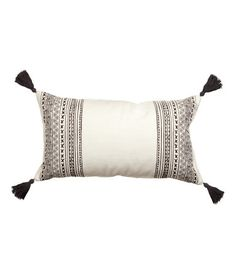 Rectangular cushion cover in woven cotton fabric with a printed pattern. Yarn tassels at corners and concealed zip.