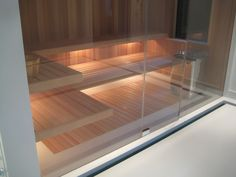 FAS built sauna with glass wall, floating benches and inset flush cedar floor slats.