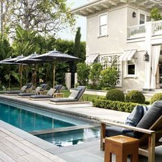 On the pool terrace of Lucky Brand Jean executives Dave DeMattei and Patrick Wade's Los Angeles home, the armchairs and chaise longues along the bluestone-edged pool are by James Perse, and the glazed ceramic side tables in the foreground are from Mecox. Moderne Pools, Design Exterior, Los Angeles Homes, Celebrity Houses, Cool Pools, Pool Houses, Pool Designs, Outdoor Rooms, Outdoor Living Spaces