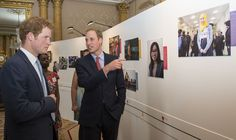 Prince Harry and Prince William, Duke of Cambridge look at images during the launch of The Queen's Young Leaders Programme at Buckingham Palace on July 9, 2014 in London, England.
