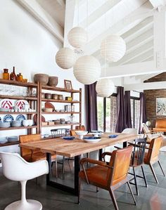 cluster of white paper lanterns hung over wood dining table / sfgirlbybay