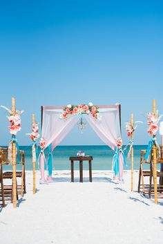 Coral and turquoise beach wedding arbor.