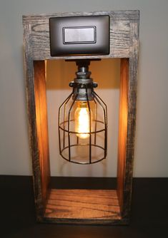 This item will be built and ready to ship in 1-2 weeks after ordered. This hand made lamp is made out of a hand stained oak . It comes with a simple light switch, outlet and 2 USB ports on the back perfect for carging any of your devices! It is constructed with industrial black iron