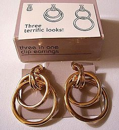 Large three styles in one hoop clip on earrings gold tone smooth mirror metal finish vintage Avon 1990 double tube intertwined rings criss cross curled top trapeze connector. In excellent original box vintage condition. Measures 1 3/4 inches long 1 1/8 inches wide.  See more vintage items here: Vintage Earrings - http://etsy.me/1HcH8nv Vintage Necklaces - http://etsy.me/1FtROPr Vintage Pins Brooches - http://etsy.me/1GU4dec Vintage Bracel...