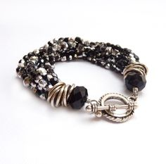 """This bracelet features eight strands of black glass fire polished beads with silver highlights with silver rondelles and chunky silver links for added texture. It's finished with a silver toggle clasp.   *8"""" long  *20mm clasp (a bit under 1"""")"""