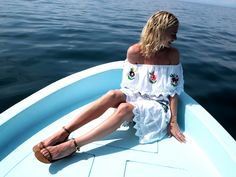 Pandora Sykes boating with dolphins in an off-the-shoulders dress & minimalist sandals