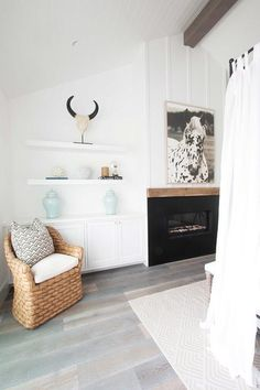 Chic bedroom features a canopy bed accented with white sheers facing a black fireplace lined with a wood mantle under a black and white horse art flanked by stacked floating shelves and built-in cabinets alongside a seagrass chair.