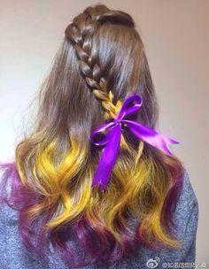 Penteado com os cabelos castanho, amarelo e roxo.