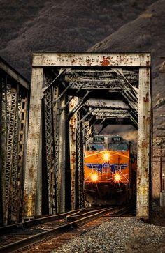 Golden Hour Crossing is a photograph by Ken Smith. Union Pacific #7780 leads a mixed freight out of Ogden, UT through the double truss bridge spanning Weber River near Morgan, UT. The golden hour is glowing and the light reflects of the rails and bridge. Soon, the sun will set for the evening. Source fineartamerica.com