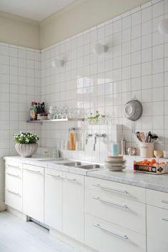 DAns l'appartement de l'amie de la designer textile Katarina Winklund, les murs de la cuisine sont tous habillés de grands carreaux blancs. Une crédence a été créée en relief pour servir d'étagère.