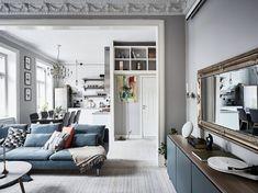 Skandinavisk inredning i vardagsrummet. Guldspegel och blå soffa.