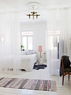 Love the use of sheer curtains to divide spaces in the room. Clever and pretty. Good idea for studio apt.: