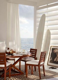 Coastal dining space decorated with surf boards and simple coastal decor