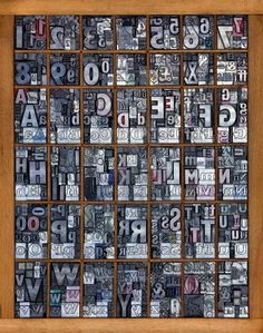 Photo of a printing tray full of old used metal letterpress in mixed fonts, all the letters of the alphabet and numbers from 0-9 mixed in with some punctuation marks and symbols. Stock Photo
