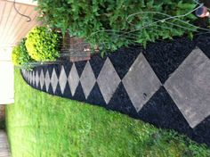 Patio stones placed corner to corner for an inexpensive walk with a curve. Finish off with black mulch.