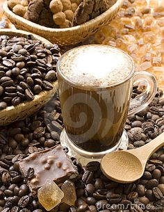 Cup of cappuccino coffee with cinnamon powder, surrounded by coffee beans, cookies, crystallized brown sugar and chocolate.