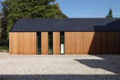 Vertical cladding with slate roof - lots of wood, small vertical windows