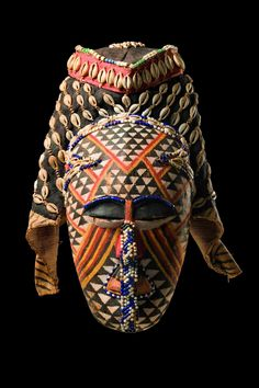 """Africa   Face mask """"ngaady a mwaash"""" from the Kuba people of DR Congo   Wood, polychrome paint, glass beads, raffia, cloth, cowrie shells   """"ngaady a mwaash"""" represents the sister and wife of """"woot"""", the progenitor of the Bushong. It is one of the three most important mask figures of the Bushong, belonged to the royal family and was used for public ceremonies or during initiation rites for young boys."""