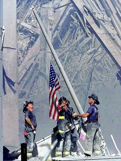 New York — Brooklyn firefighters raise an American flag at the disaster site on the day of the attacks.