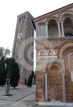 Photo made at a portion of the back of the cathedral and the bell tower in Murano in the municipality of Venice in the Veneto region (Italy). In the image you see to the left of the beautiful back with columns and decorations, detached from the church, the high bell tower with a square base, with three lights with two white columns at the height of the bells. Complete the picture some cypress.
