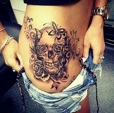 Skull tattoo with flowers and butterflies, love the placement