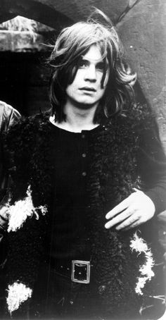 Here's one from left field : young Ozzy Osbourne: Black Sabbath. Wears black, hair, accent. Never mind the bat beheading .