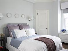 chambre grise avec un grand lit et appliques murales