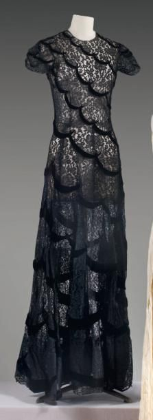 Jean PATOU Robe longue en dentelle noire ornée de ruban de velours de forme irca 1935 / 1938  Robe longue en dentelle noire ornée de ruban de velours de forme croissant cousus pour donner un effet de festoné en biais, ras du cou, petites manches, jupe ample à ourlet doublé de crin.