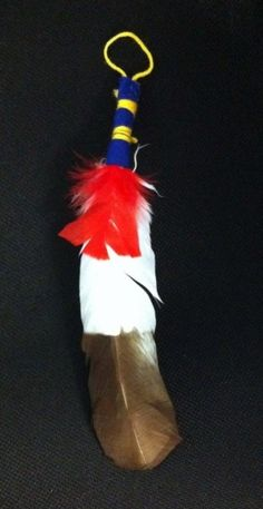 This is a real feather that has been dyed to resemble an eagle feather (it's actually a turkey feather). It has been wrapped in traditional scout colors (blue and yellow) and includes a loop to easily hang it from your Arrow of Light Award. Comes assembled. Between 10-12 inches long.