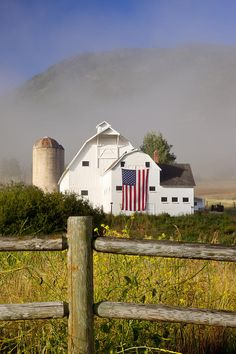 Beautiful all white barn with an American flag.