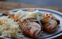 Fried Fish is a beach staple in Jamaica, topped with condiments like onions, carrots and Scotch Bonnet peppers.