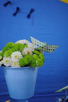 arranjo de flores brancas e verdes em vaso de alumínio azul em festa de menino. O aniversário teve o tema brinquedos de menino e os arranjos foram decorados com origamis de barquinho nas cores escolhidas: azul, verde e amarelo.