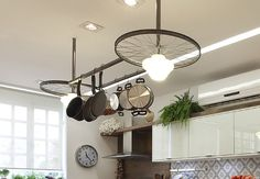 These bike wheels make a fabulous design statement - as well as supporting the kitchen lights and pan rack. #repurposed