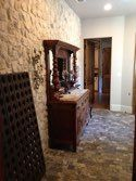 The wine serving area features the interior stone wall, cobblestone floors, antique entry door panels, a service window to the front courtyard plus small pass through access to the main kitchen. Design by Jamie Linn, constructed by Veranda Designer Homes.