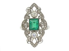 Lovely and lacy, this antique Edwardian emerald and diamond ring would make a gorgeous gossamer addition to any woman's jewel box. Crafted in fine platinum, this elongated style features a romantic openwork design set with pave diamonds. A central rectangular emerald glows green at the very center of the design while a quartet of smaller and larger bezel set diamonds accent the piece.