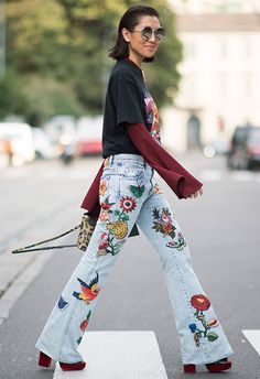 Street style shot from milan fashion week woman wearing embroidered jeans with a band t-shirt and platform boots