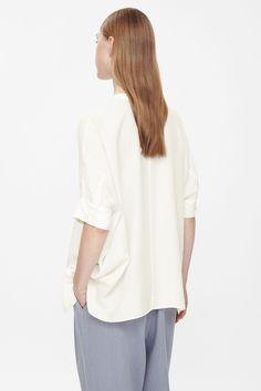 Made from pure silk that is lightweight and slightly sheer, this collarless tunic top is a wide square-cut shape. With a hidden partial button fastening, it has simple button cuffs and a softly graduated hemline.