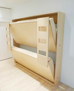neat bunk beds and a dresser with book holders on the sides.