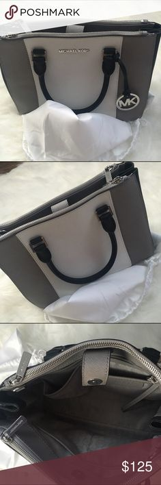 NEW Michael Kors handbag Purchased last season at my local Michael Kors store for $350 I have NEVER worn this. Has been sitting in my closet in its purchased Michael Kors coverup baggy. Excellent condition New without tags. Bag colors are silver, black and white. And bag is very comfortable and roomy. Comes with cross body strap !!! Michael Kors Bags Satchels