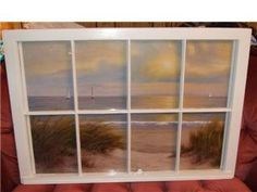 Vintage window with a seascape painting behind it.