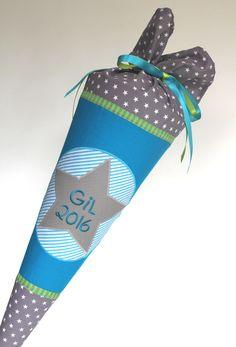 Eine schlichte Schultüte in türkis und grau, mit grüne/grauem Webband und aufgesticktem Namen. Der Schultütenbezug wird aus Baumwollstoff genäht und mit Sternapplikation verziert.Der Papprohling,...
