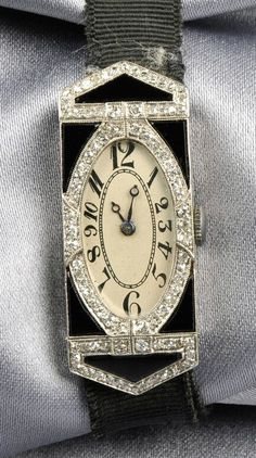 Art Deco Platinum, Onyx, and Diamond Wristwatch, the ivory-tone dial with Arabic numeral indicators, enclosing an 18-jewel manual-wind Paul Ditisheim movement, no. 100389, the case inlaid with shaped black onyx and single-cut diamond melee accents, with millegrain and engraved details, completed by a black strap.