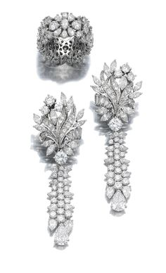 Pair of diamond pendent earrings and a ring Each earring featuring a surmount of floral design suspending a tassel motif, set with marquise-, pear-shaped, brilliant-cut and baguette diamonds; the ring designed as a wide band, similarly set. Diamond Earing, Diamond Jewelry, Chandelier Earrings, Dangle Earrings, Statement Earrings, Jewelry Sets, Fine Jewelry, Jewellery Sketches, Schmuck Design