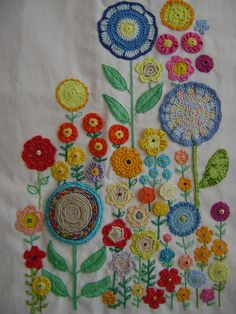 I love the combination of so many techniques in this piece! Bias tape pinwheels, Suffolk puffs, embroidery, crochet, applique and the giant flower made from twisted strips of fabric! Repeating the same shaped flowers in different techniques and similar colours brings the whole piece together instead of making it look scrappy.