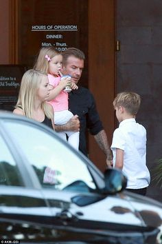 David Beckham carries daughter Harper after taking children and their nanny to dinner in Beverly Hills.  (August 2014)