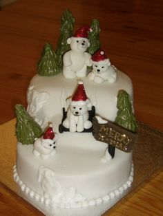 """- Christmas cake made for my friend with her family as the polar bears. 3 x 7"""" round fruit cakes covered with marzipan and sugarpaste. snow effect is royal icing, bears made from sugarpaste, hats rolled in disco dust, trees are marzipan cones and royal icing leaves made with medium petal tip."""