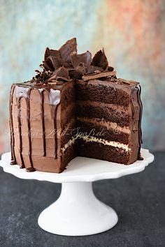 Rezept für Dreifarbige Schokotorte. Eine sehr schokoladige Torte aus Schokoböden, Schokoganache, Schokoguss und Schokodekoration. Die Schokolade ist überall.