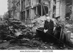World War 2, Battle of Berlin, May 1945. Two elderly German men, one wearing the armband signifying blindness, the other his helper, sitting on a crate amid the rubble. Photo by Yevgeny Khaldei.